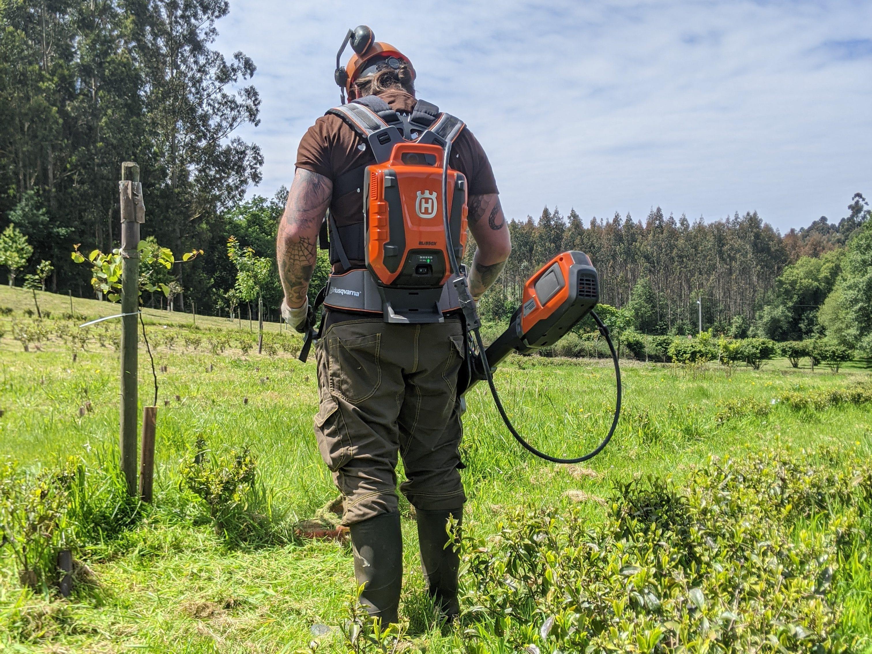 Hombre utilizando maquinaria a batería Husqvarna en el campo